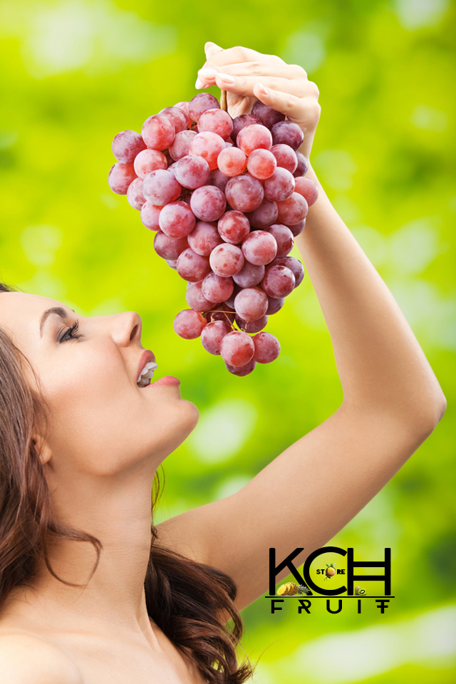 A-woman-playfully-eating-grapes.jpg